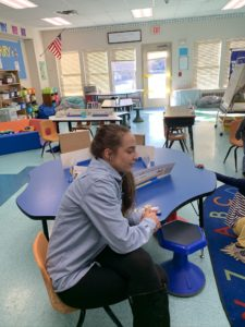 paraeducator at the desk with students